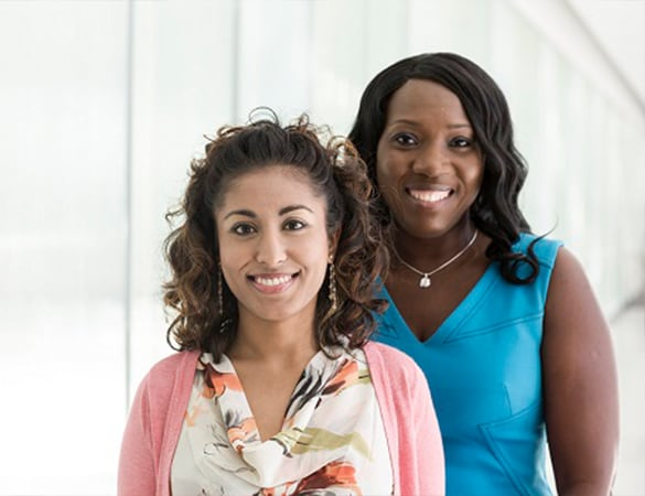 Two woman standing next to each other smiling