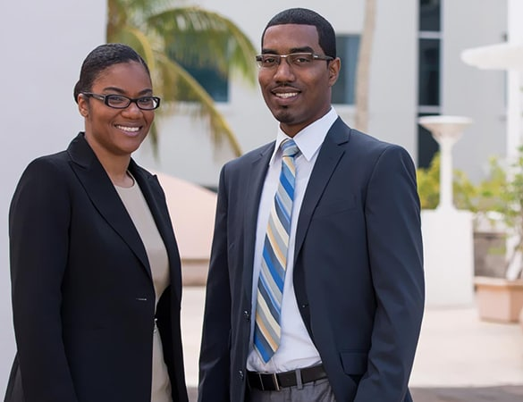 A man and a woman both in black blazers smiling