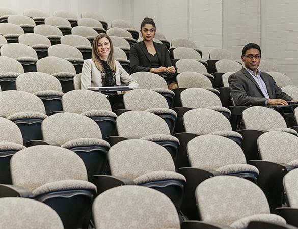 Three people sitting in an auditorium