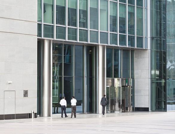 Three men standing infront of a glass building