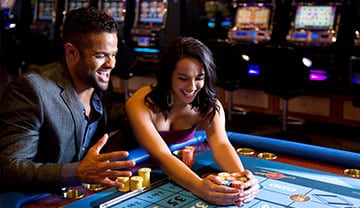 A man and a woman grabbing casino chips from a table
